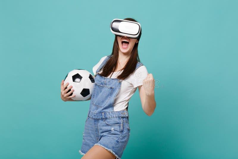 Ευτυχής οπαδός ποδοσφαίρου γυναικών στη σφαίρα ποδοσφαίρου εκμετάλλευσης κασκών, που σφίγγει την πυγμή όπως το νικητή που απομονώ στοκ φωτογραφία με δικαίωμα ελεύθερης χρήσης