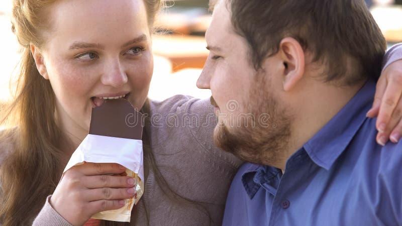 Ευτυχής σοκολάτα δαγκώματος ζευγών αγάπης και να σπρώξει με τη μουσούδα, υψηλά τρόφιμα ζάχαρης, τρυφερότητα στοκ φωτογραφίες
