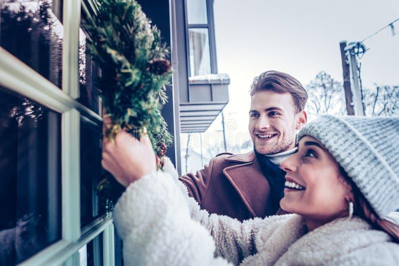 Ευτυχής σύζυγος που αισθάνεται την κατάπληξη διακοσμώντας το σπίτι με το στεφάνι στοκ φωτογραφίες με δικαίωμα ελεύθερης χρήσης