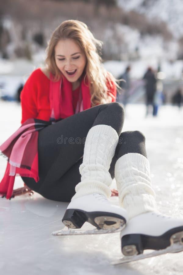 Ευτυχής συνεδρίαση κοριτσιών στον πάγο Πατινάζ πάγου γυναικών υπαίθριο στοκ εικόνα με δικαίωμα ελεύθερης χρήσης