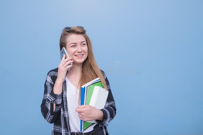 Ευτυχής σπουδαστής που μιλά σε ένα smartphone και που κοιτάζει μακριά, που απομονώνεται σε ένα μπλε υπόβαθρο Copyspace στοκ φωτογραφία