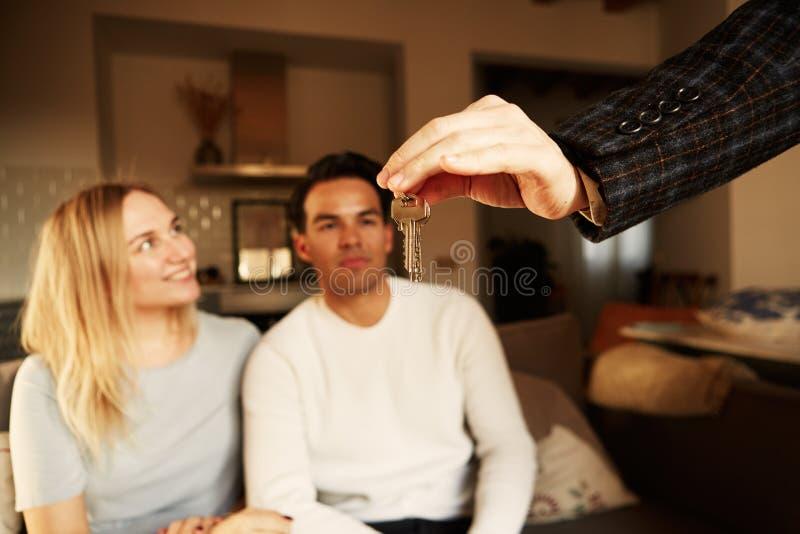 Ευτυχής παρουσίαση ζευγών χαμόγελου νέα κλειδιά του καινούργιου σπιτιού τους στοκ εικόνες με δικαίωμα ελεύθερης χρήσης