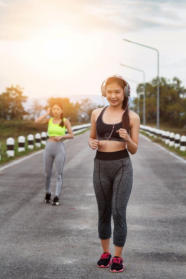 Ευτυχή και όμορφα joggers γυναικών που τρέχουν στο δρόμο Ικανότητα και έννοια Workout Wellness στοκ φωτογραφία