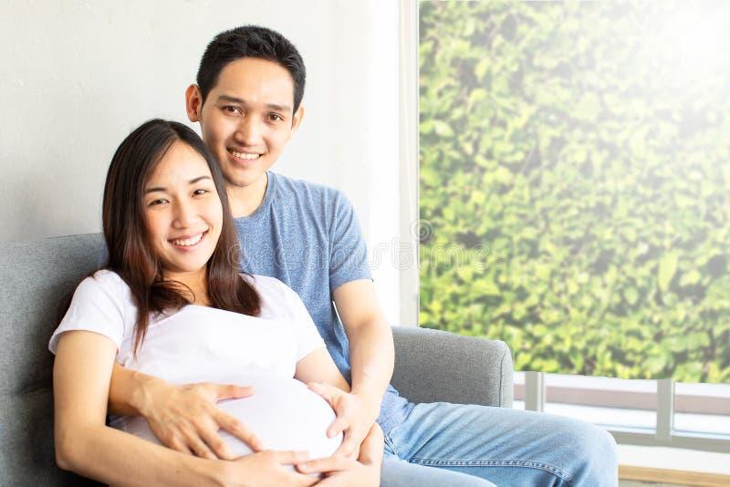 Ευτυχείς σύζυγος και έγκυος γυναίκα που αναμένουν τη συνεδρίαση γέννησης στον καναπέ στο καθιστικό στοκ εικόνα με δικαίωμα ελεύθερης χρήσης
