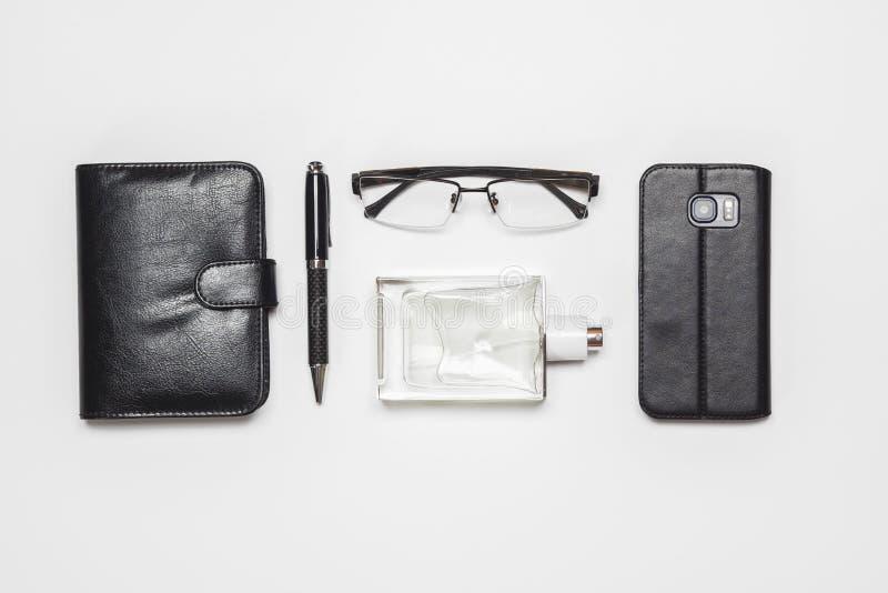 Επίπεδος βάλτε τη τοπ άποψη gentlemen' εξαρτήματα του s στο άσπρο υπόβαθρο Eyeglasses, αρώματα, smartphone, μάνδρα, σημειωματ στοκ φωτογραφία με δικαίωμα ελεύθερης χρήσης