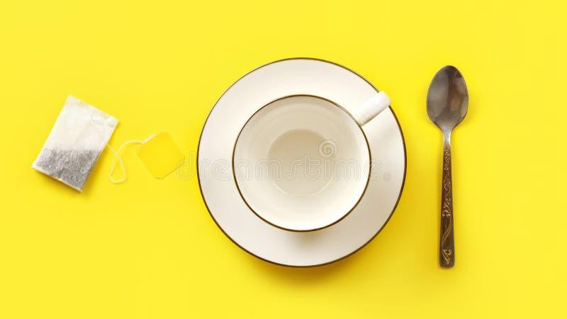 Επίπεδος βάλτε τη φωτογραφία, την τσάντα τσαγιού, το κενά φλυτζάνι πορσελάνης και το κουτάλι στον κίτρινο πίνακα στοκ εικόνες
