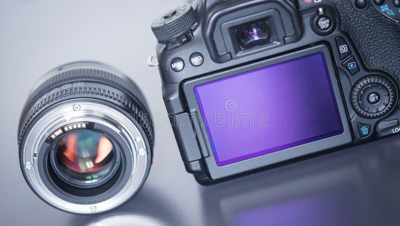 Επαγγελματίας που φωτογραφίζει: Πίσω άποψη μιας επαγγελματικής ανακλαστικής κάμερας και ενός φακού φωτογραφιών στοκ φωτογραφία