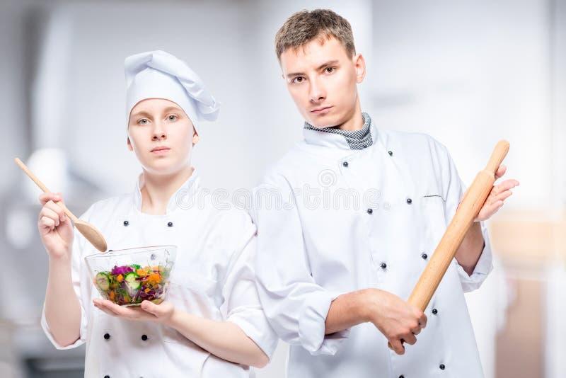 επαγγελματικοί μάγειρες ζευγών με τη σαλάτα και την κυλώντας καρφίτσα στοκ φωτογραφίες
