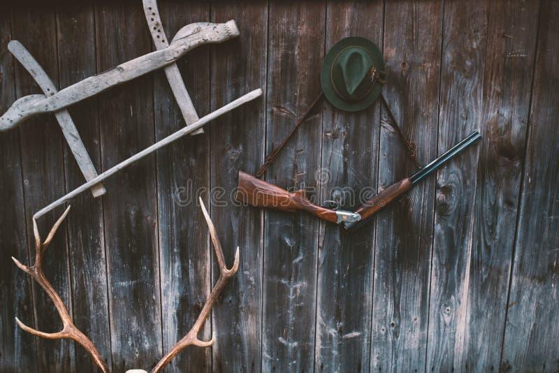 Επαγγελματικός εξοπλισμός κυνηγών για Τουφέκι, ελάφια, τρόπαιο ελαφιών αυγοτάραχων sculs και άλλα σε ένα ξύλινο μαύρο υπόβαθρο Sc στοκ φωτογραφίες