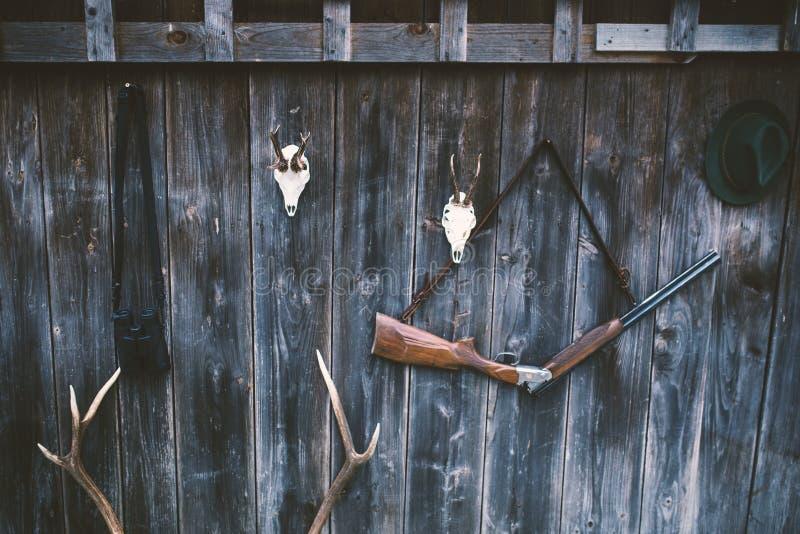 Επαγγελματικός εξοπλισμός κυνηγών για Τουφέκι, ελάφια, τρόπαιο ελαφιών αυγοτάραχων sculs και άλλα σε ένα ξύλινο μαύρο υπόβαθρο Sc στοκ εικόνες