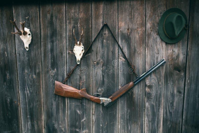 Επαγγελματικός εξοπλισμός κυνηγών για Τουφέκι, ελάφια, τρόπαιο ελαφιών αυγοτάραχων sculs και άλλα σε ένα ξύλινο μαύρο υπόβαθρο Sc στοκ εικόνα