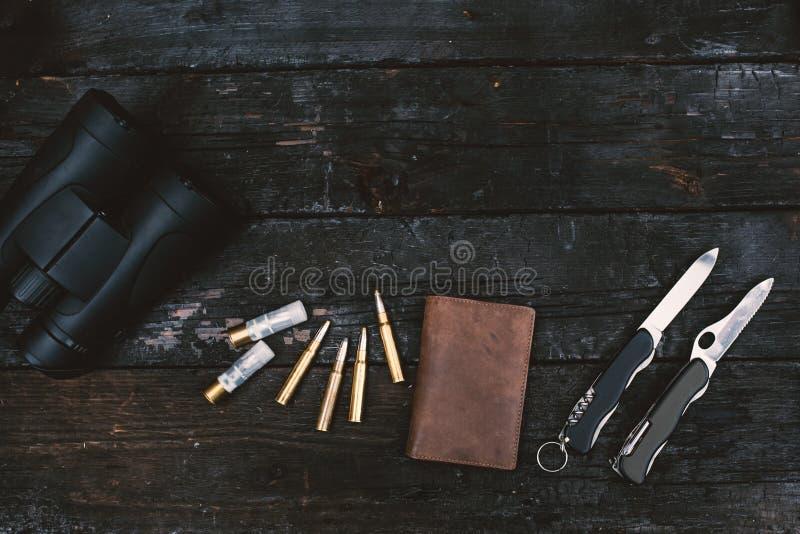 Επαγγελματικός εξοπλισμός κυνηγών για Τουφέκι, μαχαίρια, τρόπαιο sculps, πυρομαχικά, και άλλα σε ένα ξύλινο μαύρο υπόβαθρο Tro στοκ εικόνες