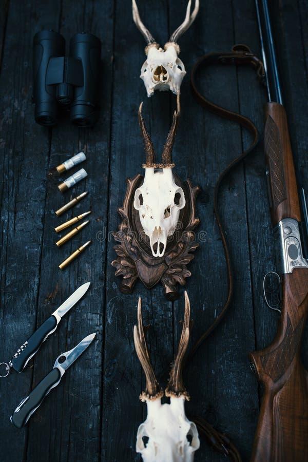 Επαγγελματικός εξοπλισμός κυνηγών για Τουφέκι, μαχαίρια, τρόπαιο sculps, πυρομαχικά, και άλλα σε ένα ξύλινο μαύρο υπόβαθρο Tro στοκ φωτογραφίες