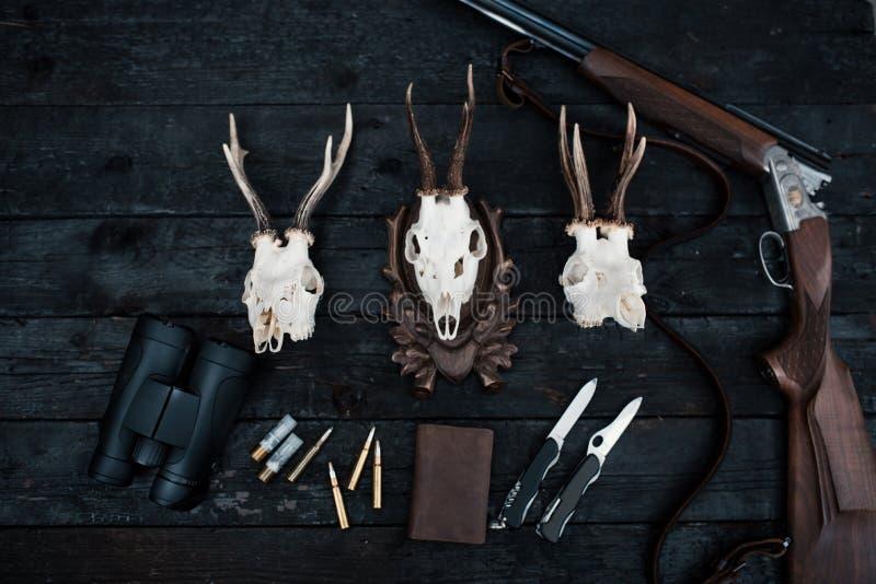 Επαγγελματικός εξοπλισμός κυνηγών για Τουφέκι, μαχαίρια, τρόπαιο sculps, πυρομαχικά, και άλλα σε ένα ξύλινο μαύρο υπόβαθρο Tro στοκ εικόνες με δικαίωμα ελεύθερης χρήσης