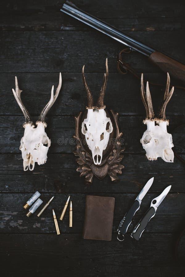 Επαγγελματικός εξοπλισμός κυνηγών για Τουφέκι, μαχαίρια, τρόπαιο sculps, πυρομαχικά, και άλλα σε ένα ξύλινο μαύρο υπόβαθρο Tro στοκ εικόνα με δικαίωμα ελεύθερης χρήσης