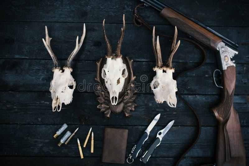 Επαγγελματικός εξοπλισμός κυνηγών για Τουφέκι, μαχαίρια, τρόπαιο sculps, πυρομαχικά, και άλλα σε ένα ξύλινο μαύρο υπόβαθρο Tro στοκ φωτογραφία