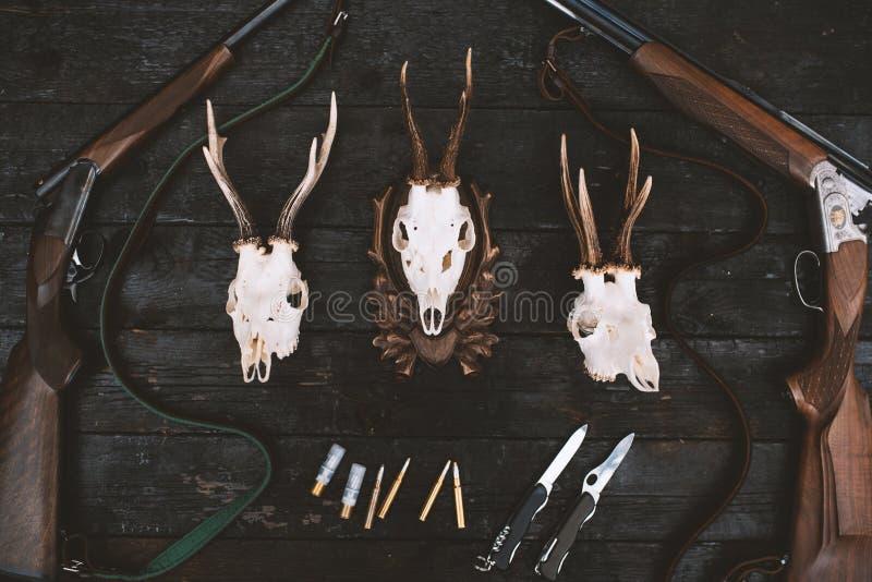 Επαγγελματικός εξοπλισμός κυνηγών για Τουφέκι, μαχαίρια, τρόπαιο sculps, πυρομαχικά, και άλλα σε ένα ξύλινο μαύρο υπόβαθρο Tro στοκ φωτογραφία με δικαίωμα ελεύθερης χρήσης