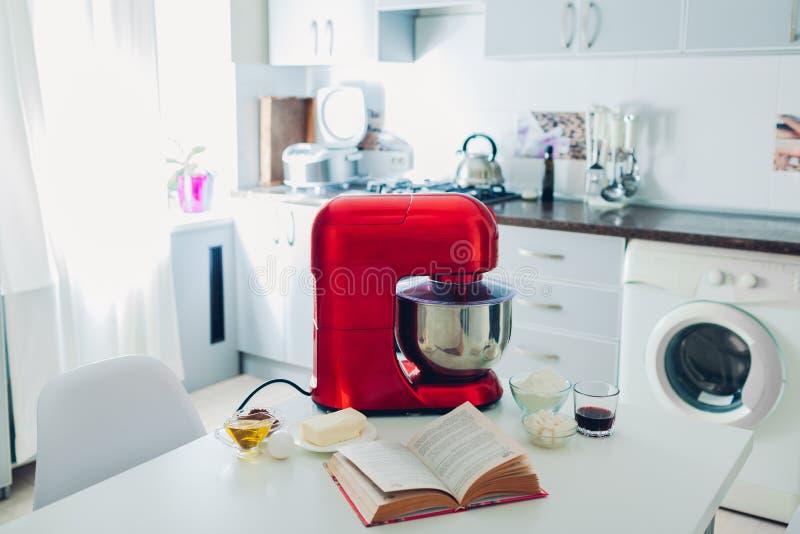 Επεξεργαστής τροφίμων με τα συστατικά και μαγειρικό βιβλίο στην κουζίνα στοκ φωτογραφία