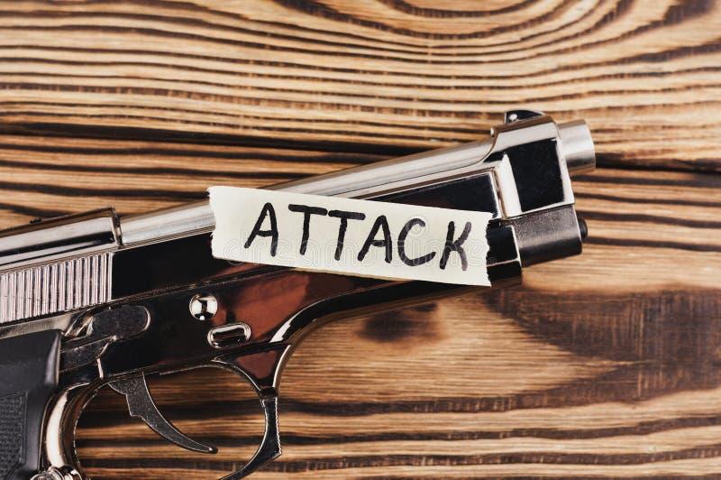ΕΠΙΘΕΣΗ επιγραφής σε σχισμένο χαρτί και το στιλπνό πιστόλι στοκ φωτογραφία