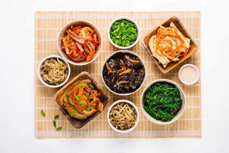 Επιλογή των κορεατικών ασιατικών τροφίμων στα κύπελλα στο χαλί μπαμπού στοκ φωτογραφία