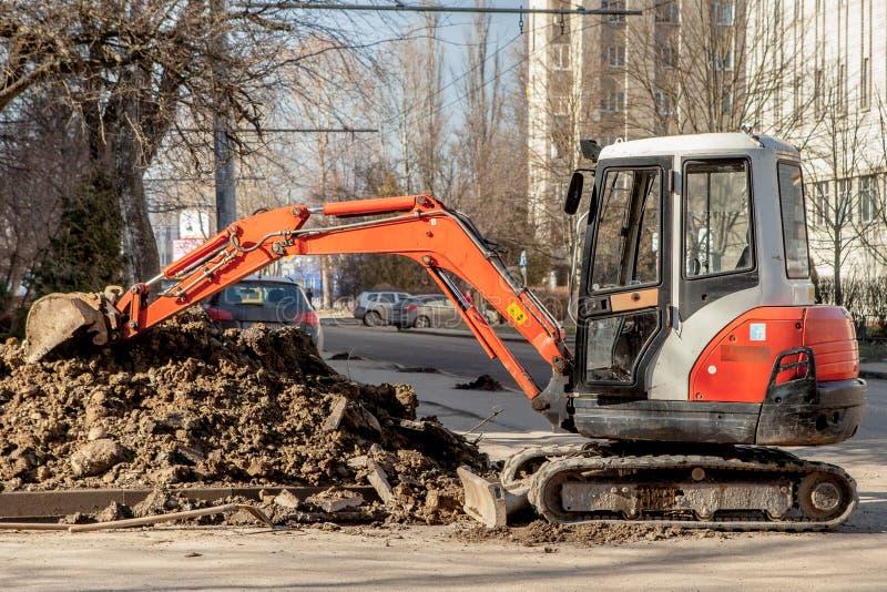 Επισκευή των επικοινωνιών πόλεων Εγκατάσταση σωληνώσεων Ένας πορτοκαλής εκσκαφέας έσκαψε μια τάφρο για τους παλαιούς σωλήνες αντι στοκ φωτογραφίες με δικαίωμα ελεύθερης χρήσης