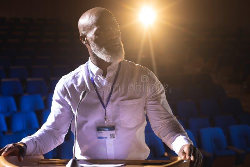 Επιχειρηματίας που κοιτάζει και που σκέφτεται στεμένος στη σκηνή στην αίθουσα συνεδριάσεων στοκ φωτογραφίες με δικαίωμα ελεύθερης χρήσης