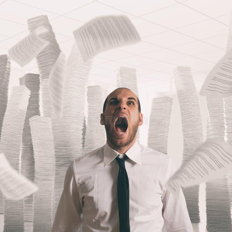 Επιχειρηματίας που τονίζονται και καταπονημένη κραυγή στην αρχή με τα πετώντας φύλλα εγγράφου στοκ εικόνα με δικαίωμα ελεύθερης χρήσης