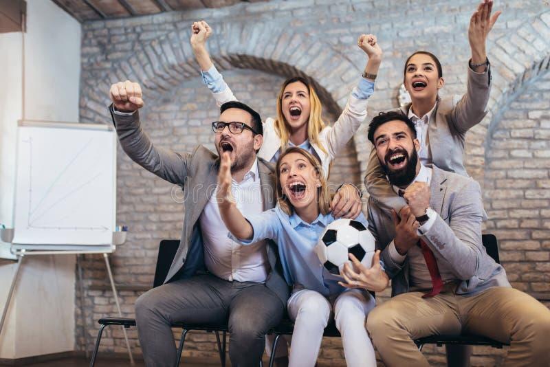 Επιχειρηματίες ή οπαδοί ποδοσφαίρου που προσέχουν το ποδόσφαιρο στη TV και που γιορτάζουν τη νίκη Φιλία, αθλητισμός και έννοια ψυ στοκ φωτογραφία