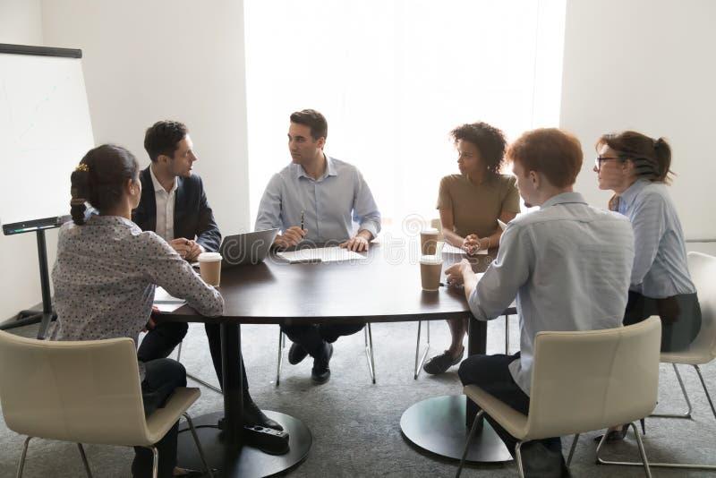 Επιχειρηματίες που συζητούν το επιχειρησιακό πρόγραμμα στη multiethnic συνεδρίαση στη αίθουσα συνδιαλέξεων στοκ φωτογραφίες