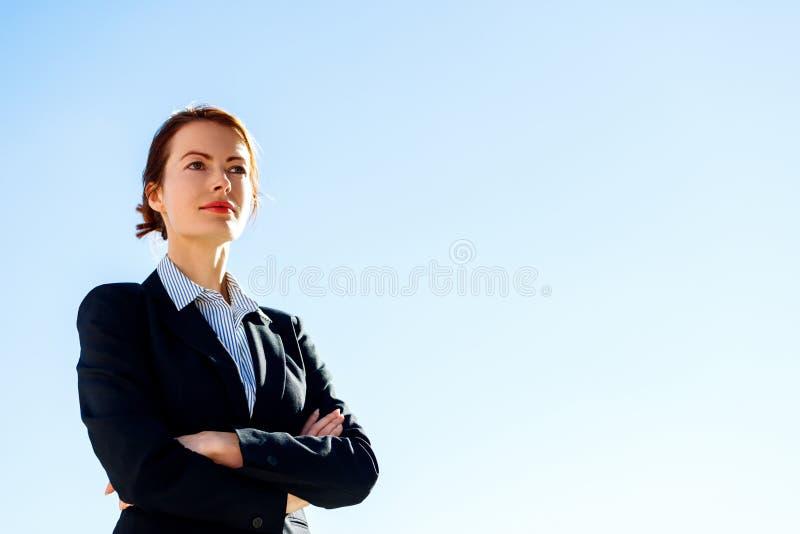 Επιχειρησιακή γυναίκα με τις διασχισμένες στάσεις χεριών ενάντια στο σαφή μπλε ουρανό στοκ φωτογραφία με δικαίωμα ελεύθερης χρήσης