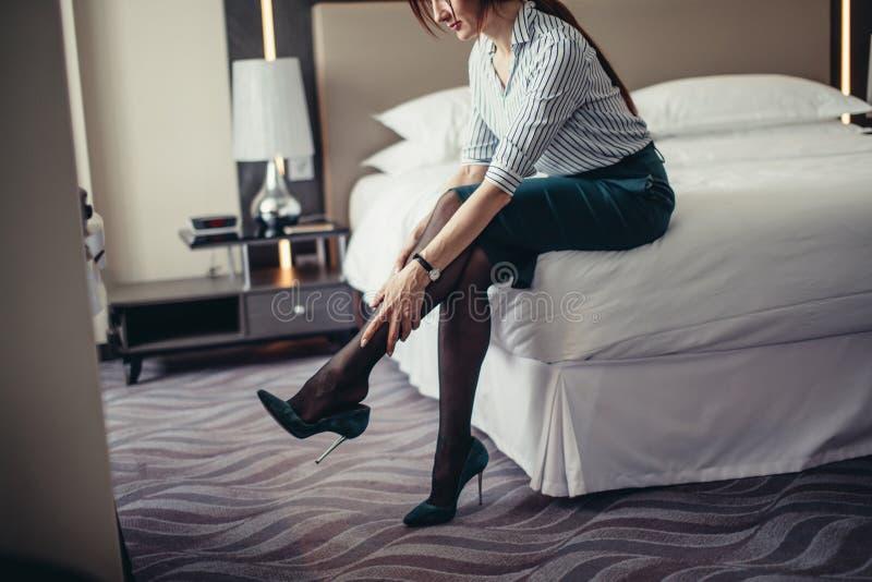 Επιχειρησιακή κυρία που κουράζεται μετά από ένα μακρύ ταξίδι που στηρίζεται στο κρεβάτι στο δωμάτιο ξενοδοχείου στοκ φωτογραφίες