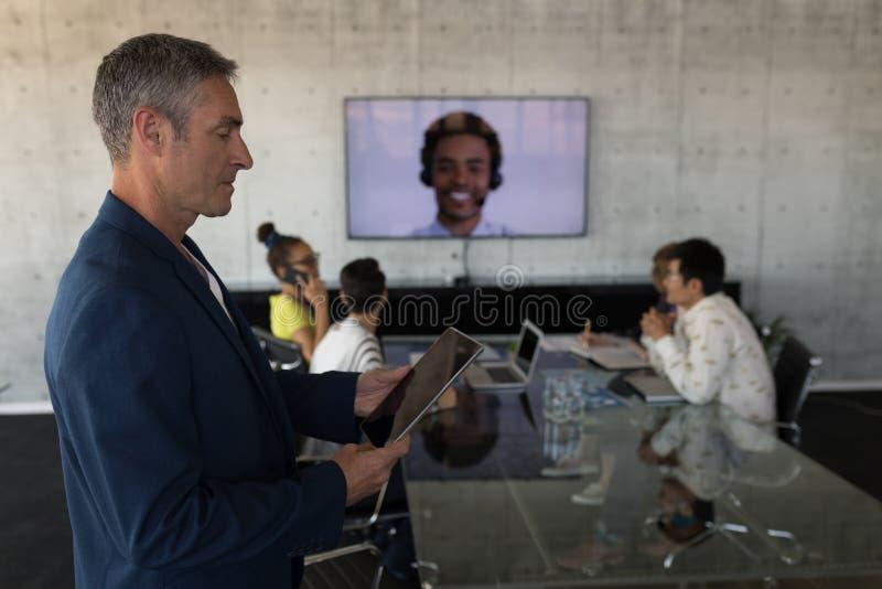 Επιχειρησιακή ομάδα που εργάζεται μαζί σε μια τηλεοπτική κλήση στο δωμάτιο πινάκων στοκ φωτογραφία με δικαίωμα ελεύθερης χρήσης