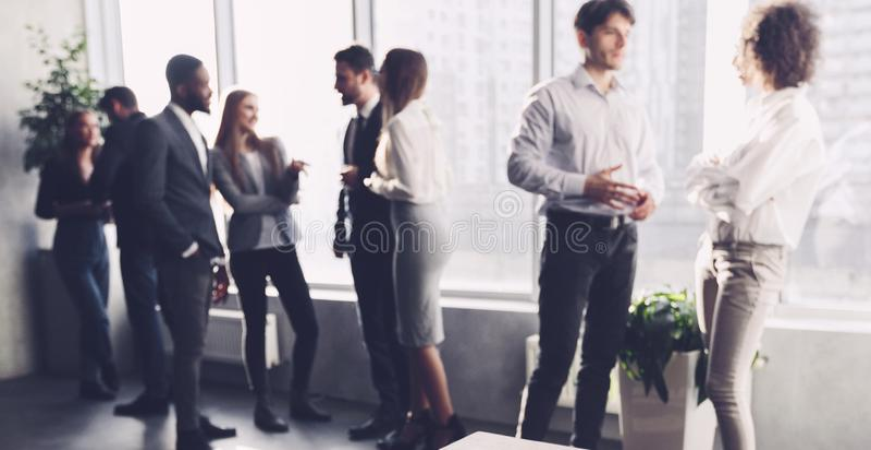 Επιχειρησιακοί συνάδελφοι που έχουν το σπάσιμο, που μιλά κοντά στο παράθυρο στοκ εικόνα