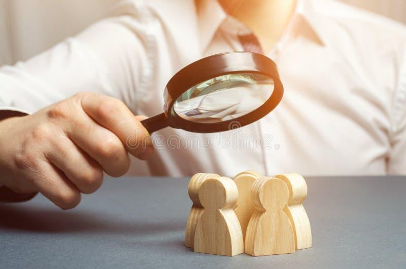 Επιχειρησιακός ηγέτης που κρατά μια ενίσχυση - γυαλί πέρα από μια ομάδα των εργαζομένων Η έννοια της εύρεσης των νέων υπαλλήλων T στοκ εικόνες