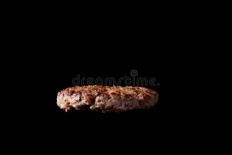 Επιπλέον ψημένο στη σχάρα burger patty απομόνωσε το μαύρο υπόβαθρο στοκ εικόνες