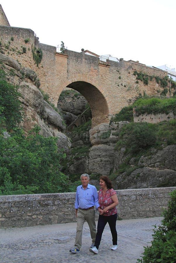 Ζεύγος τουριστών που περπατά κοντά στη γέφυρα Puente Nueve στη Ronda στοκ φωτογραφία με δικαίωμα ελεύθερης χρήσης