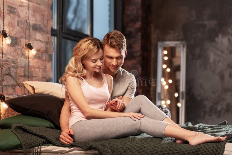 Ζεύγος που φορά τις πυτζάμες που ξοδεύουν το χαλαρώνοντας χρόνο στην κρεβατοκάμαρα στοκ φωτογραφία με δικαίωμα ελεύθερης χρήσης