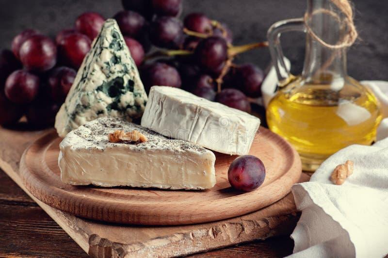 ζωή τυριών ακόμα Τυρί maasdamer, brie, camembert, vinograd, MED στοκ φωτογραφία