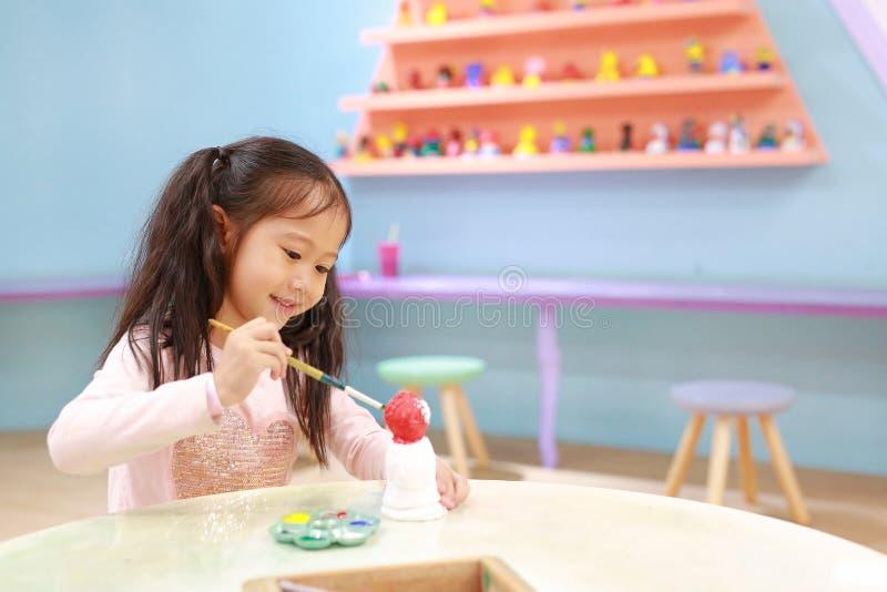 Ζωγραφική παιδιών, μικρό κορίτσι πορτρέτου που έχει τη διασκέδαση για να χρωματίσει στην κούκλα στόκων εσωτερική στοκ εικόνες