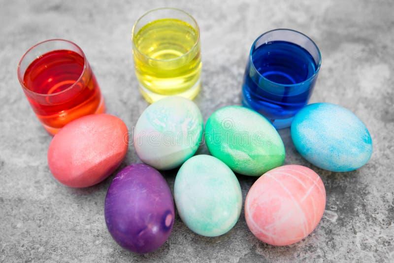 Ζωηρόχρωμα αυγά Πάσχας και γυαλιά με τις χρωστικές ουσίες αυγών στο γκρίζο υπόβαθρο στοκ φωτογραφία με δικαίωμα ελεύθερης χρήσης