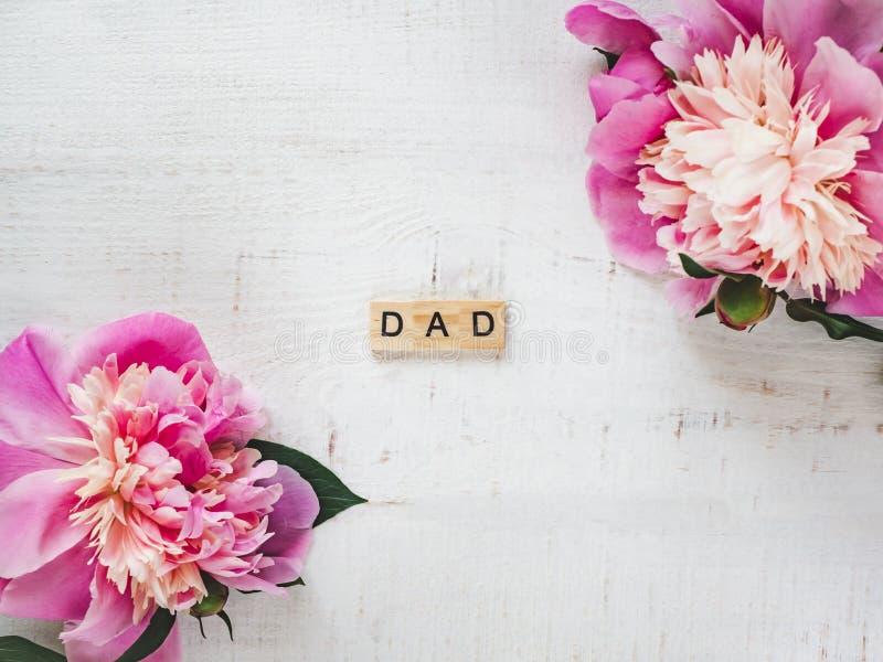 Ζωηρόχρωμα peonies και DAD λέξης σε ένα άσπρο υπόβαθρο στοκ φωτογραφίες