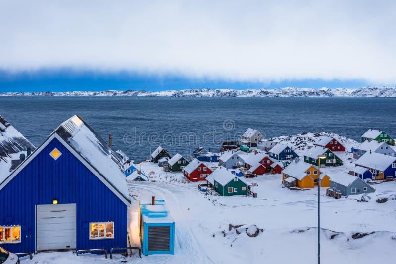 Ζωηρόχρωμες καλύβες inuit μεταξύ των βράχων και χιόνι στο φιορδ σε ένα προάστιο του αρκτικού κύριου Νουούκ, Γροιλανδία στοκ φωτογραφίες