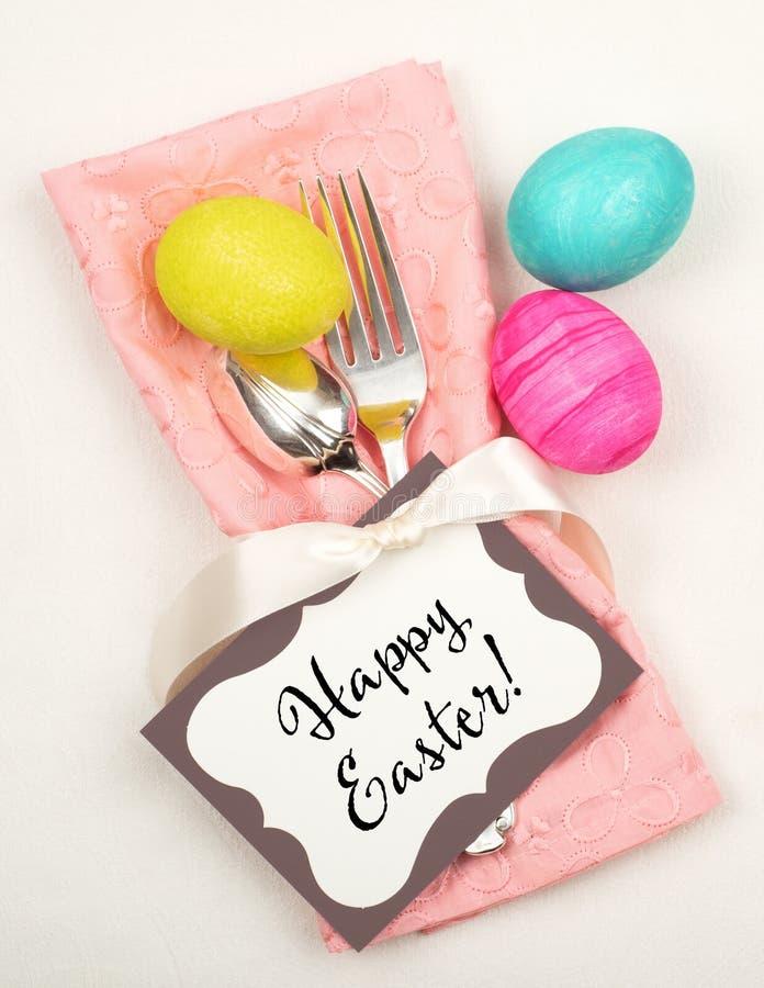 Ζωηρόχρωμος πίνακας αυγών Πάσχας που θέτει με τις ασημικές, βαμμένα αυγά, ρόδινη πετσέτα, κάρτα επάνω από το άσπρο ύφασμα στοκ φωτογραφίες