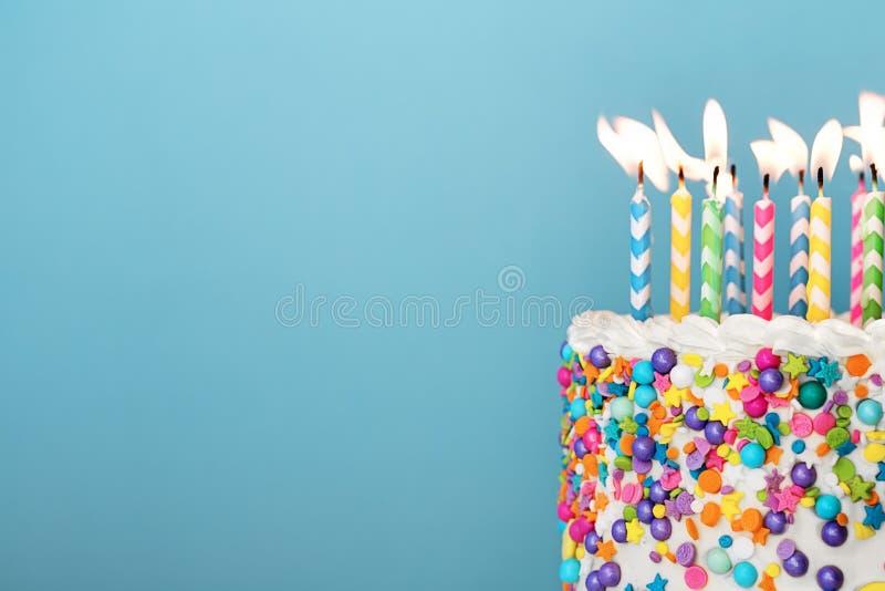 Ζωηρόχρωμο κέικ γενεθλίων με τα μέρη των κεριών στοκ εικόνα