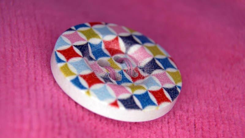 Ζωηρόχρωμο κουμπί στο ρόδινο ύφασμα στοκ φωτογραφία με δικαίωμα ελεύθερης χρήσης