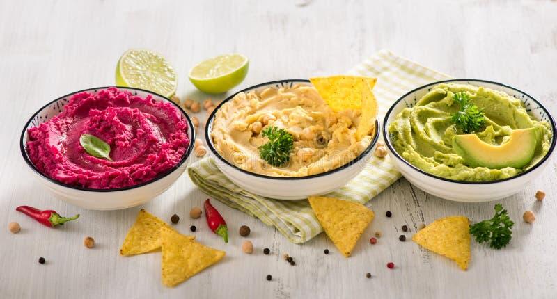 Ζωηρόχρωμο hummus, διαφορετικές εμβυθίσεις, vegan hummus πρόχειρων φαγητών, παντζαριών και αβοκάντο, χορτοφάγος κατανάλωση στοκ φωτογραφία με δικαίωμα ελεύθερης χρήσης