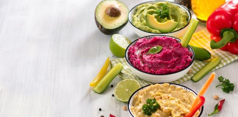 Ζωηρόχρωμο hummus, vegan hummus πρόχειρων φαγητών, παντζαριών και αβοκάντο, χορτοφάγος που τρώνε, διαστημικό υπόβαθρο αντιγράφων στοκ εικόνες