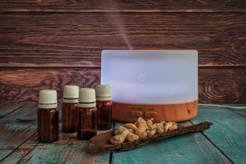 Ηλεκτρικός διασκορπιστής πετρελαίου με τα μπουκάλια και frankincense, οριζόντιο σχήμα στοκ φωτογραφία με δικαίωμα ελεύθερης χρήσης