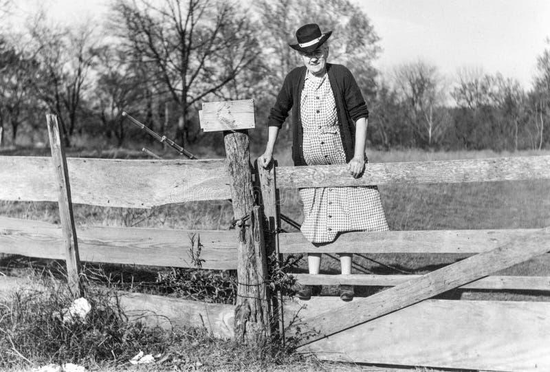 Ηλικιωμένη κυρία που αναρριχείται στο φράκτη με αλιεύοντας Πολωνούς στις αρχές του 1900 το s στοκ φωτογραφίες