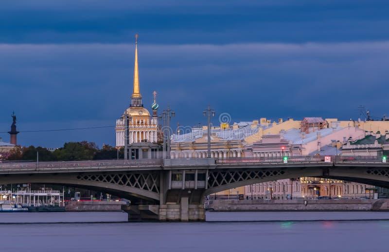 Ηλιοβασίλεμα σε Άγιο Πετρούπολη πέρα από τον ποταμό Neva με την άποψη της γέφυρας Blagoveshchenskiy και του κώνου ναυαρχείου ή Ad στοκ εικόνες